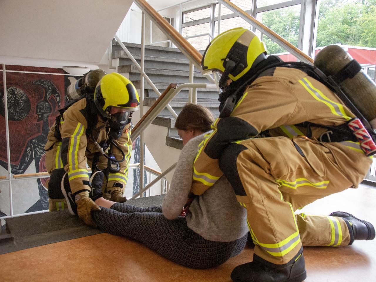 Brandweermensen oefening in trappenhuis