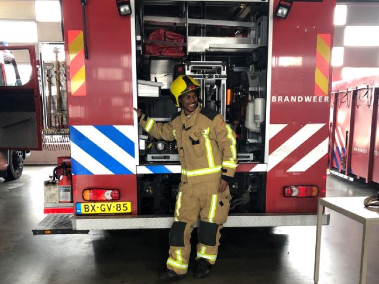 Inburgeraar gekleed als brandweerman poseert voor brandweerwagen