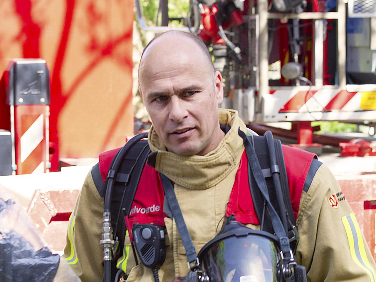 Brandweerman Marinus van Dam in bluspak houdt helm vast