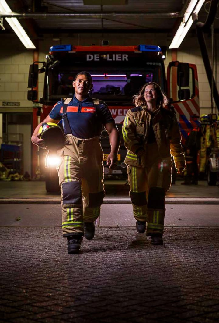 Vrijwilligers brandweer lopen in bluspak richting camera