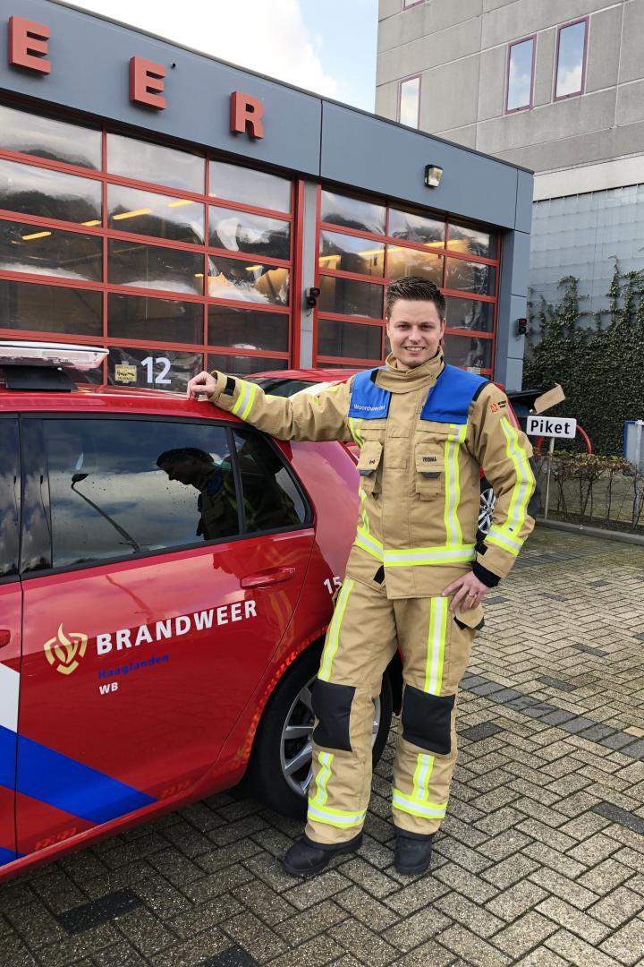 Brandweerman Mike van Velzen poseert naast brandweerauto