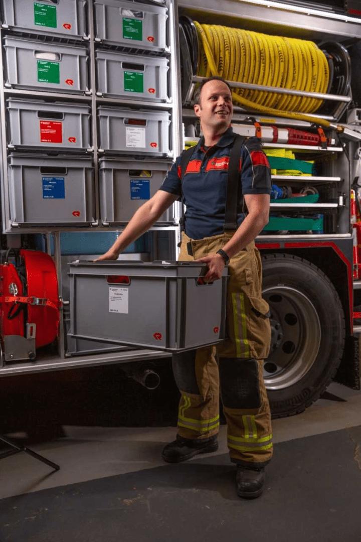 Brandweerman Gideon poseert naast brandweerwagen