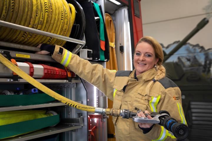 Brandweervrijwilliger Marije poseert voor brandweerwagen
