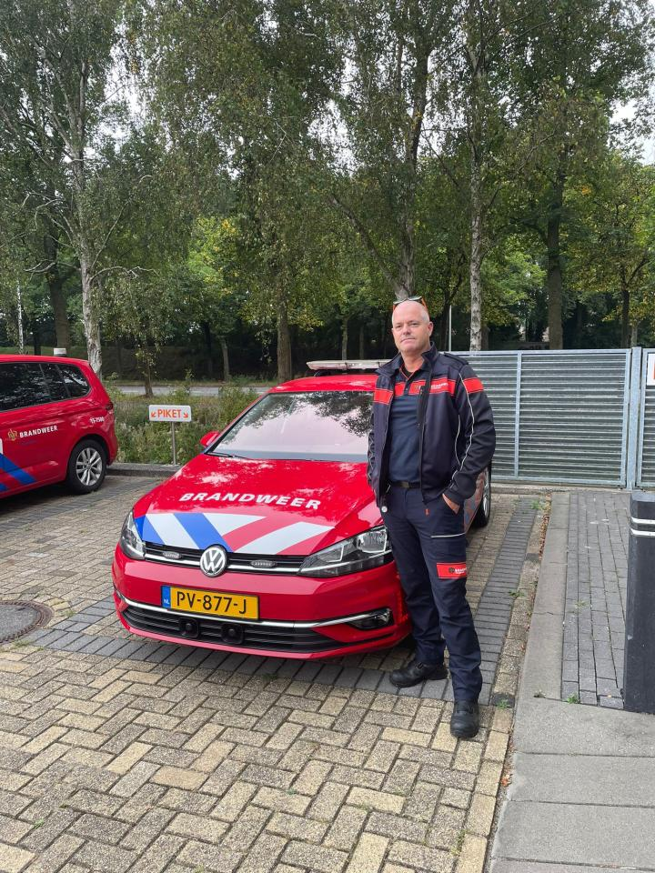 Collega Thierry poseert bij auto van de brandweer