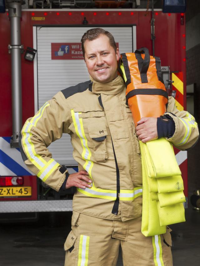 Brandweerman Christiaan poseert voor brandweerwagen met blusslang op zijn schouder