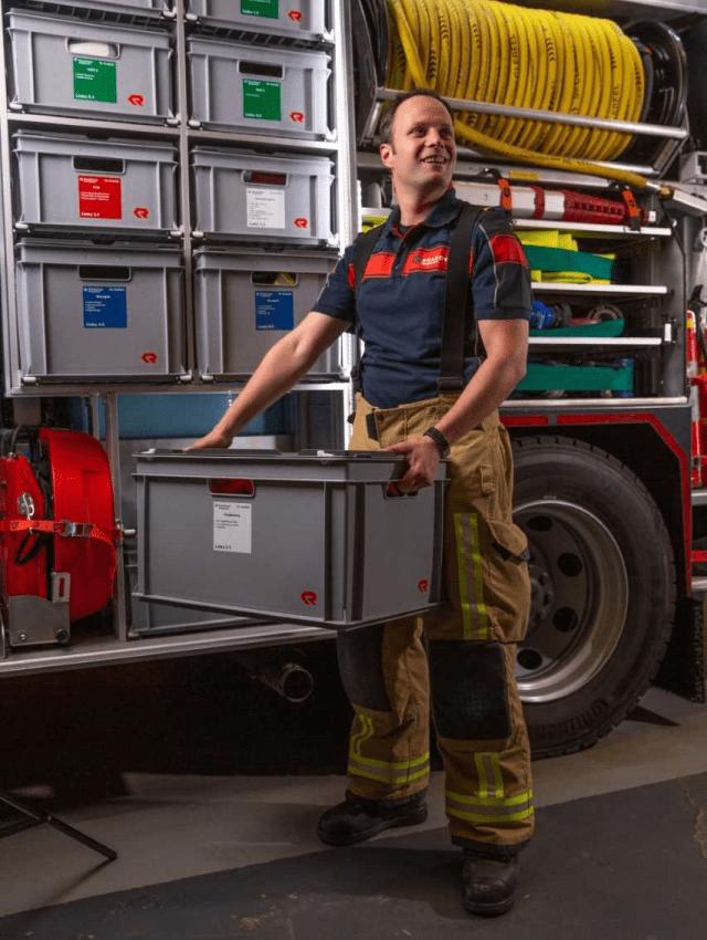 Brandweervrijwilliger Gideon poseert met krat in zijn hand bij een brandweerwagen